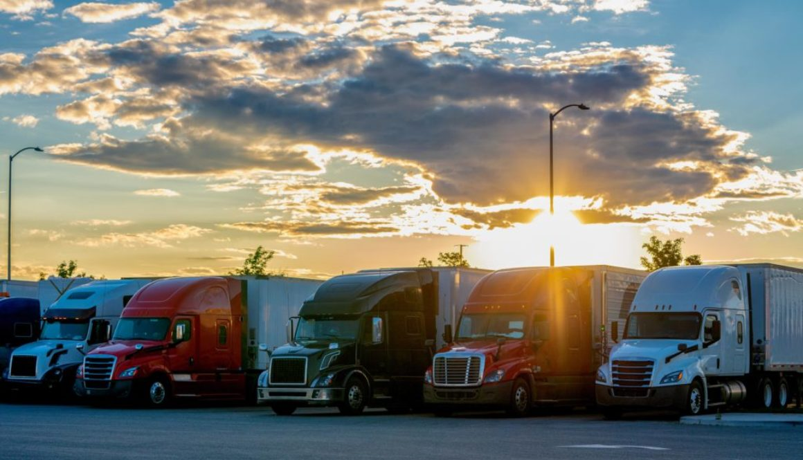 Colorful Semis Closely Parked Side By Side In A Parking Lot With A Beautiful Colorado Sunset Behind Them
